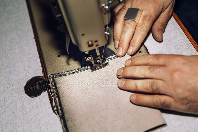 Male worker sewing bag — Stock Photo