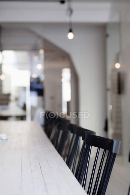 Sillas en fila en la mesa de comedor - foto de stock