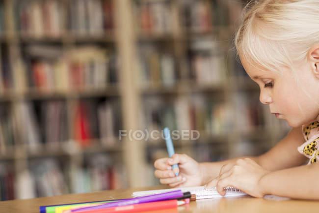 Ragazza colorazione allo scrittorio in aula — Foto stock