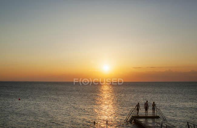 Amis debout sur le quai au-dessus de la mer — Photo de stock
