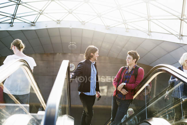 Men conversing on escalator — Stock Photo
