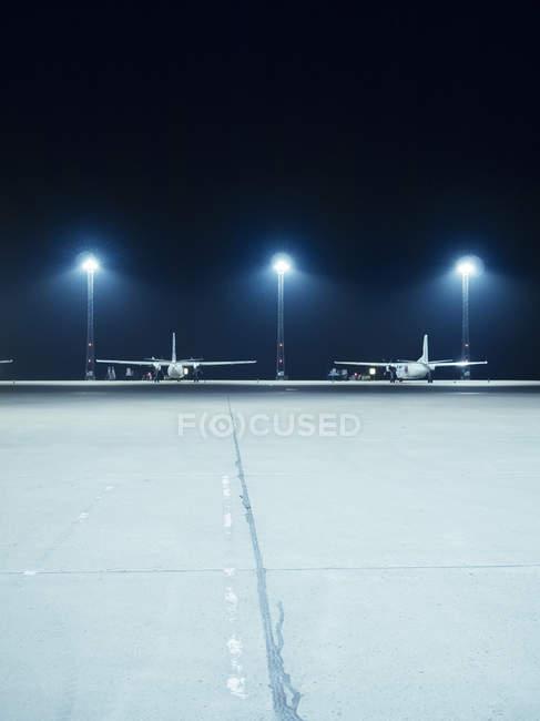 Projecteurs éclairés devant les avions — Photo de stock