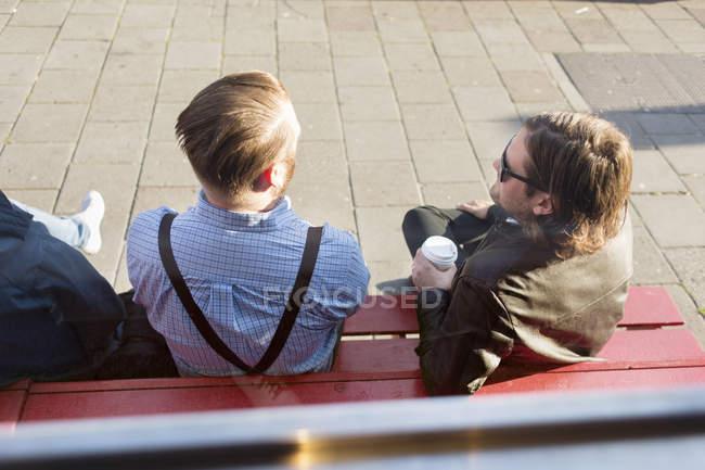 Homens que sentam-se no banco ao ar livre — Fotografia de Stock