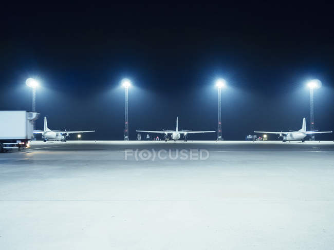 Illuminated floodlights in front of airplanes — Stock Photo