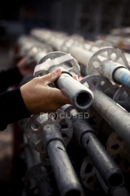 Builder selecting pipe at construction site — Stock Photo