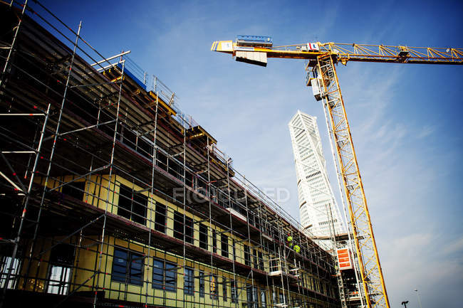 Crane in front of building under construction — Stock Photo