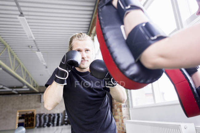 Young man with trainer practicing boxing — Stock Photo