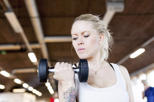 Young woman lifting dumbbell — Stock Photo