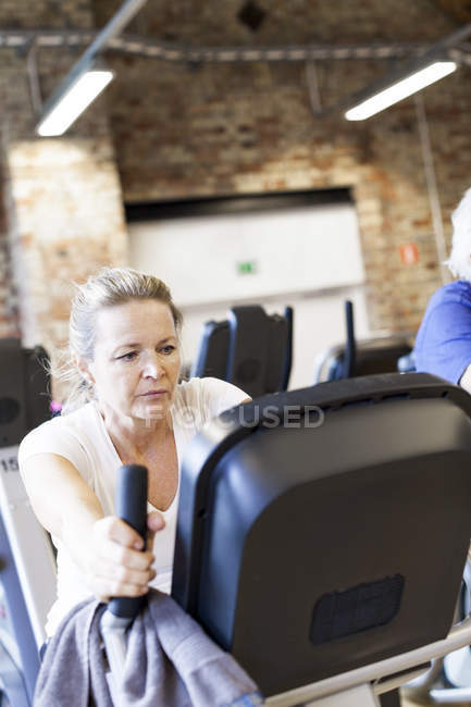 Mature woman working out on exercise bike — Stock Photo