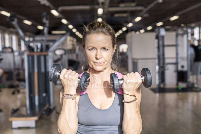Onfident mature woman lifting dumbbells — Stock Photo