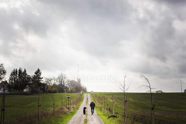 Uomo che cammina con cane su strada sterrata — Foto stock