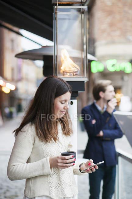 Женщина с чашкой кофе и мобильным телефоном — стоковое фото