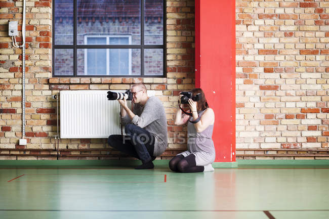 Man and woman photographing in dance studio — Stock Photo