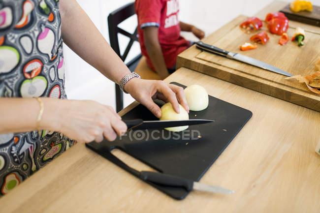 Mãe picar cebola na cozinha — Fotografia de Stock