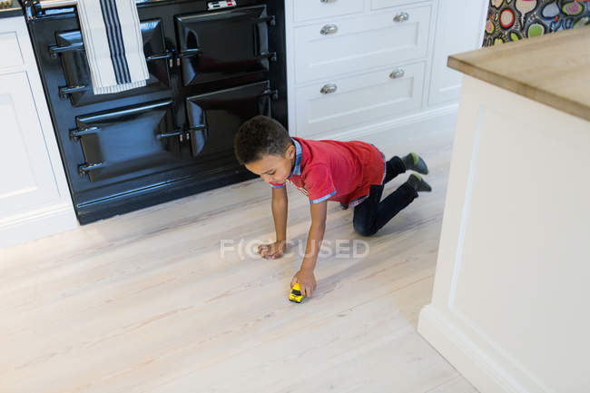 Мальчик играет с игрушечной машиной на кухне — стоковое фото