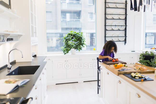 Menina cortando tomate na cozinha — Fotografia de Stock