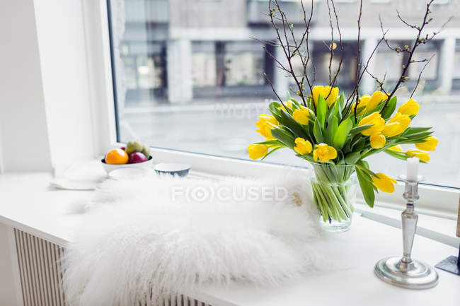 Fur rug and flower vase — Stock Photo