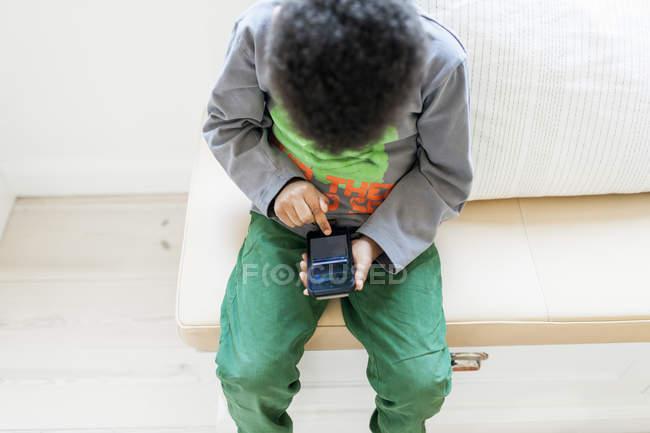 Niño jugando en el teléfono inteligente - foto de stock