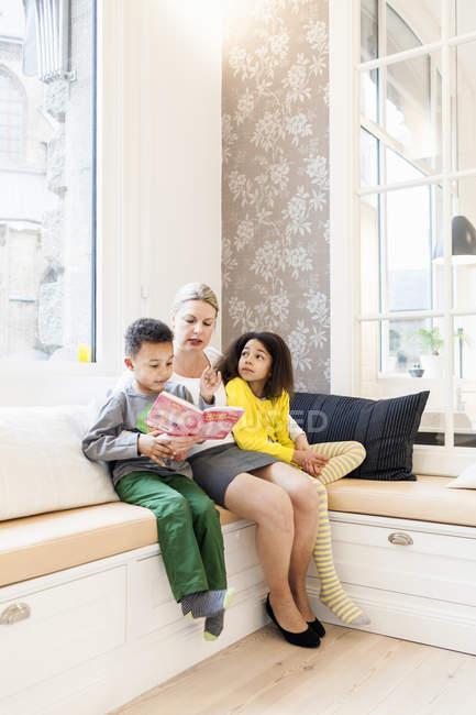 Crianças ouvindo mãe ler livro de história — Fotografia de Stock