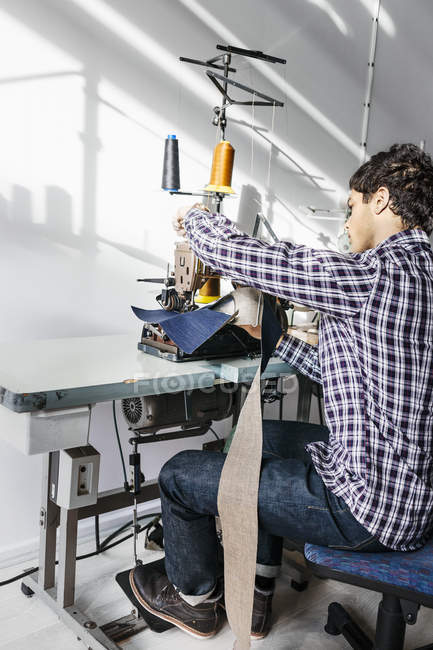 Tailor sewing jeans in factory — Stock Photo