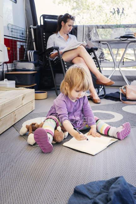 Neonata scrivendo sul blocchetto per appunti — Foto stock