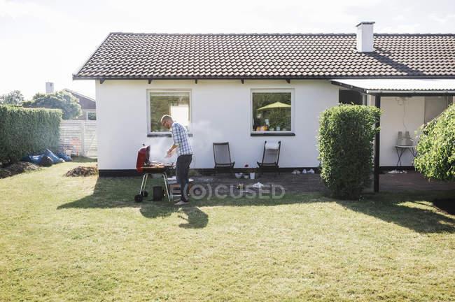 Homme griller de la nourriture à l'extérieur maison — Photo de stock
