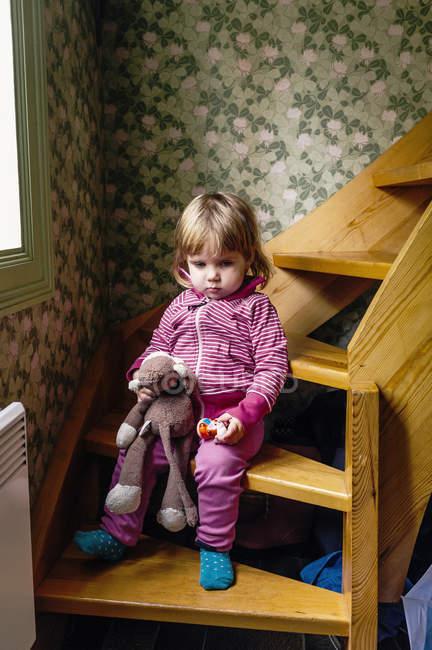 Дівчинка тримає іграшки, сидячи на дії. — стокове фото