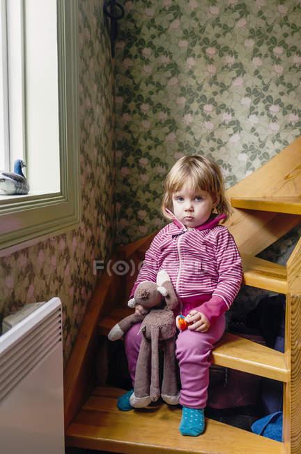 Mädchen hält Spielzeug während es auf Stufen sitzt — Stockfoto