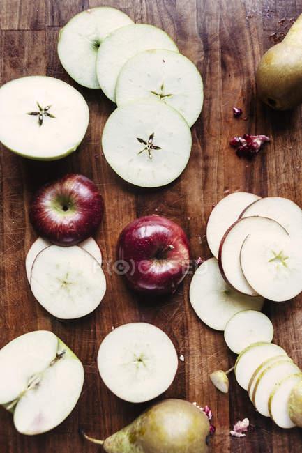 Rodajas de manzana y pera en la tabla de cortar - foto de stock