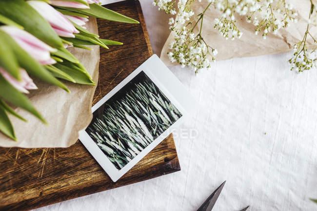Квіти в папір та фотографії на стіл — стокове фото