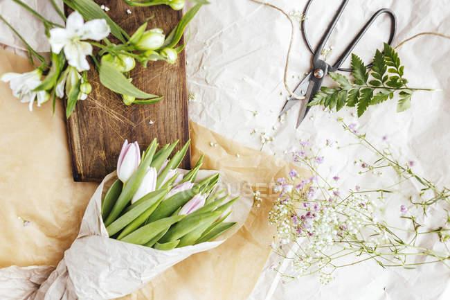 Blumen am Tisch über weißen Tisch decken — Stockfoto