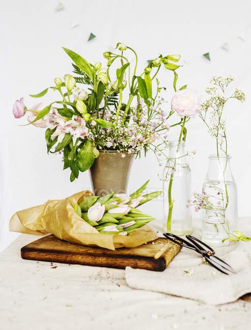 Цветы в вазе и на бумаге — стоковое фото