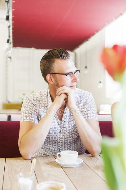 Мужчина отводит взгляд, сидя в кафе — стоковое фото