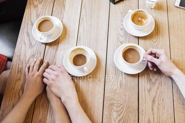 Coppia che si tiene per mano mentre prende il caffè — Foto stock