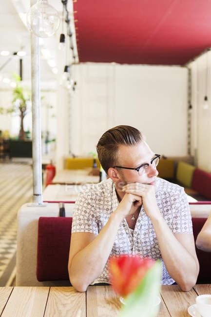 Uomo che osserva via, stando seduti al café — Foto stock