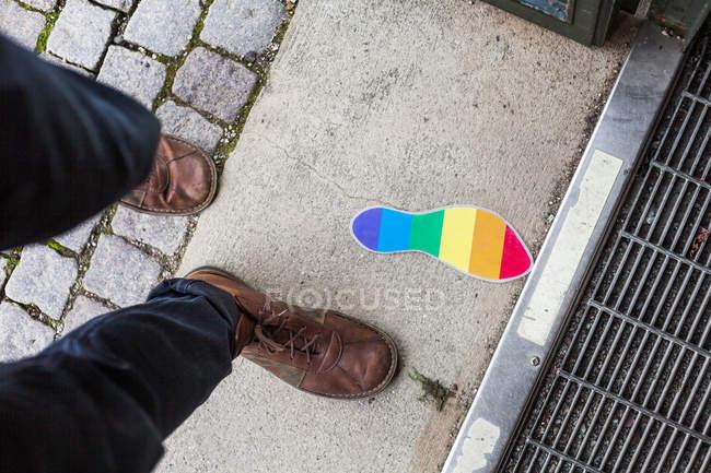 Человек идет по контуру флаг радуги — стоковое фото
