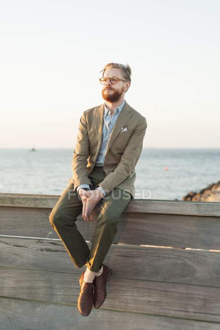 Человек, сидящий на подпорной стене — стоковое фото