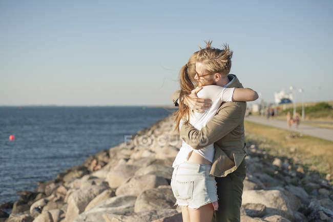 Amorosa pareja abrazándose en la playa rocosa - foto de stock