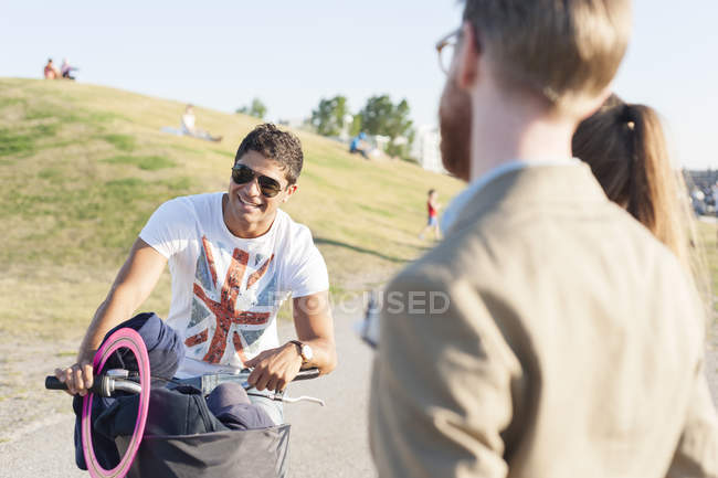 Man on bicycle with friends — Stock Photo