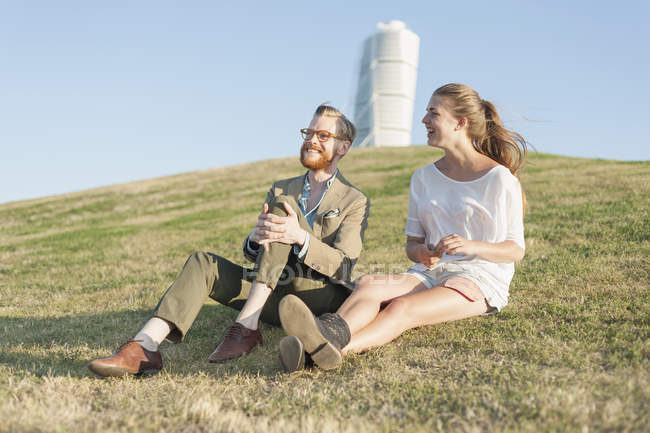 Couple sitting on grassy hill — Stock Photo