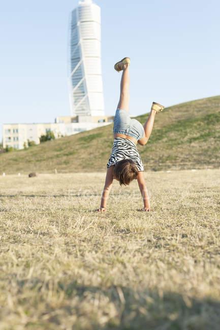 Petite fille faisant le handstand — Photo de stock