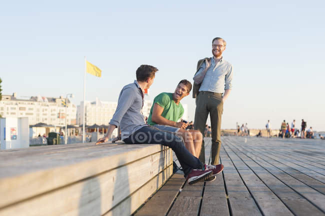 Friends at retaining wall in park — Stock Photo