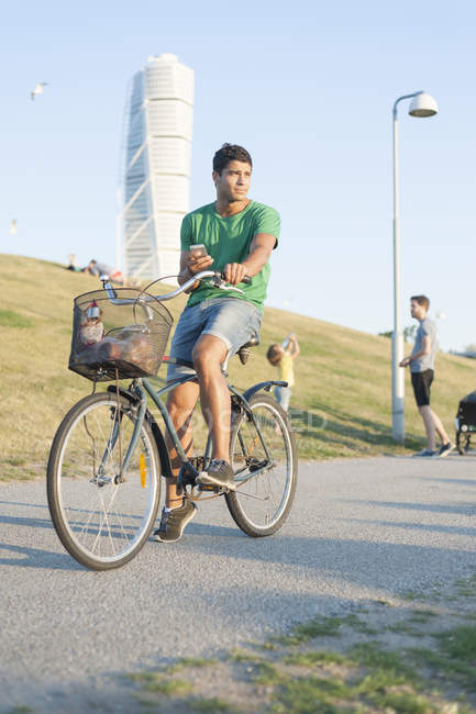 Young man riding bicycle — Stock Photo