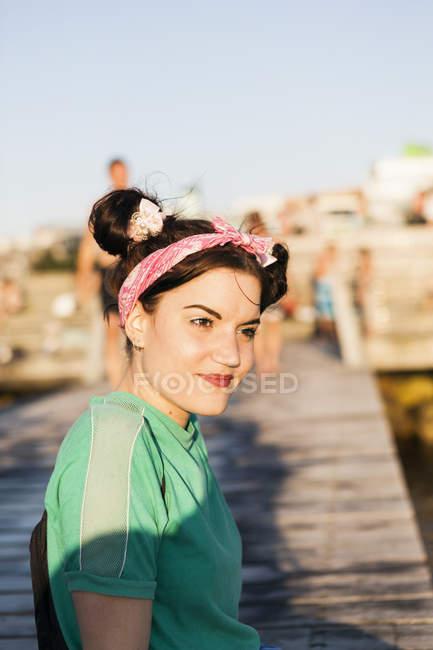 Junge Frau sitzt am pier — Stockfoto