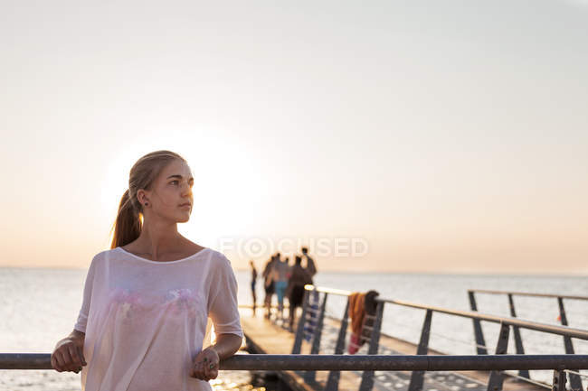Young woman leaning on railing at pier — Stock Photo