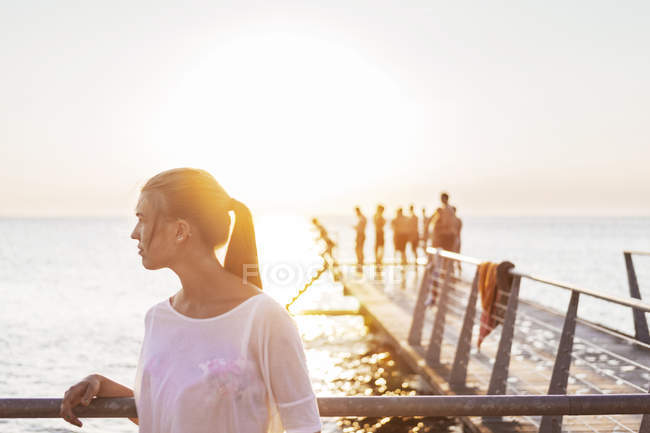 Young woman standing by railing — Stock Photo