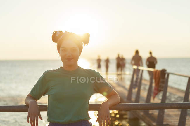 Confident young woman leaning on railing — Stock Photo