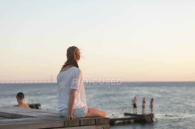 Молода жінка, сидячи на пристані — стокове фото
