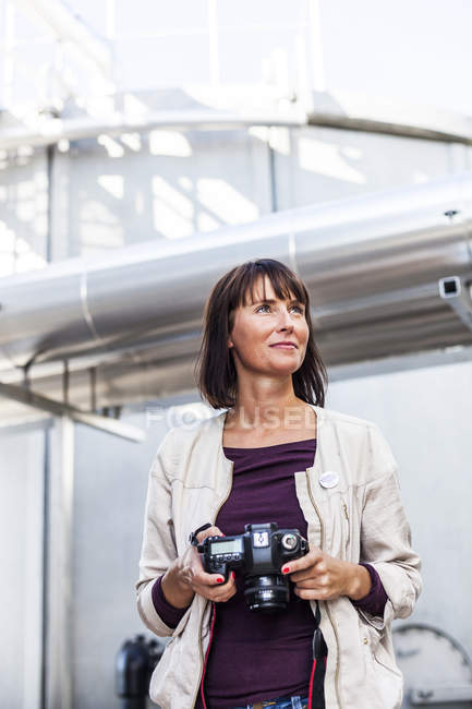 Woman holding digital camera — Stock Photo