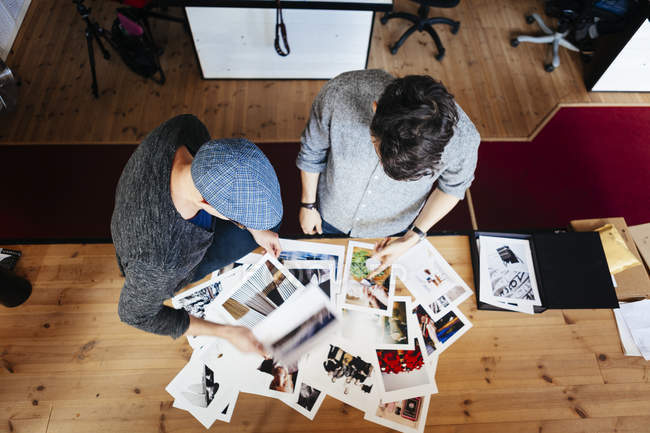 Businessmen analyzing photographs — Stock Photo